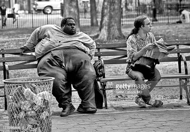 Thompkins square Park, Manhattan NYC A park bench, a garbage can 2 men and the latest news. An obese man sits on a bench gazing outward.