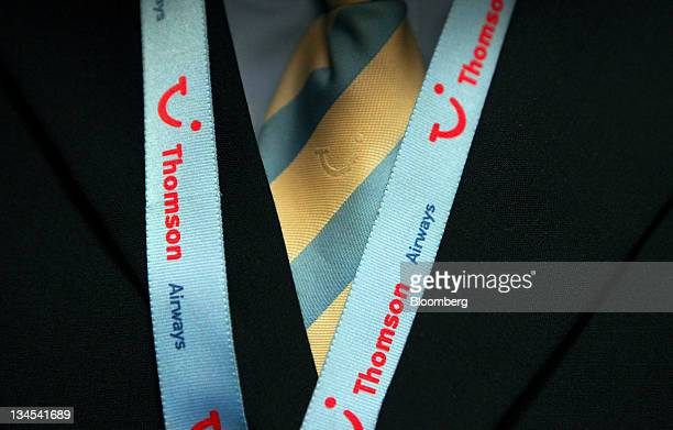 A Thomson airways flight attendant wears a branded tie and a security lanyard part of the Tui Travel Plc brand while onboard a flight at Manchester...