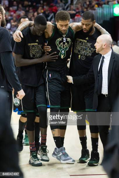 Thon Maker and Greg Monroe help Michael Beasley of the Milwaukee Bucks off the court after Beasley was injured during the first half against the...