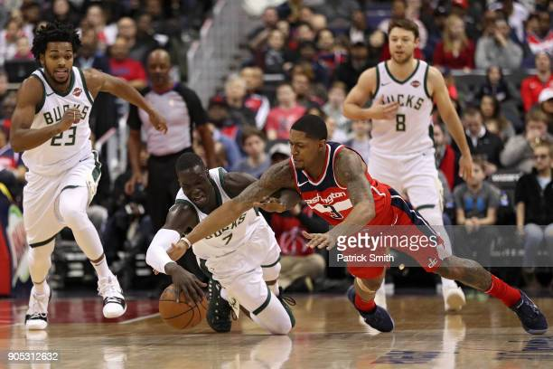 Thon Maker of the Milwaukee Bucks and Bradley Beal of the Washington Wizards battle for a loose ball during the first half at Capital One Arena on...