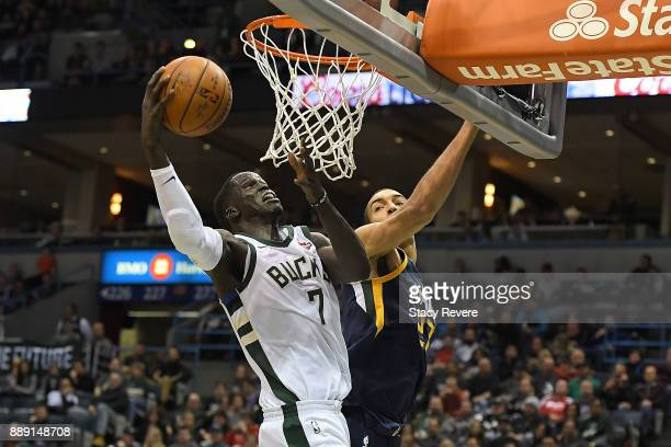 Thon Maker of the Milwaukee Bucks shoots over Rudy Gobert of the Utah Jazz during the second half of a game at the Bradley Center on December 9 2017...