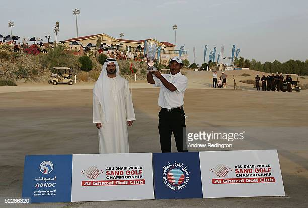 Thongchai Jaidee of Thailand R receives the trophy from Sheikh Dr Ahmed Bin Saif Al Hahyan after winning the tournament at the first playoff hole...