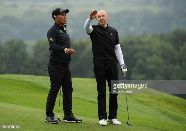 Thongchai Jaidee of Thailand speaks with former footballer Steve Stone during the pro am ahead of the British Masters at Close House Golf Club on...