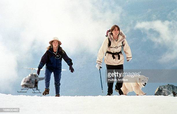 Thora Birch and Vincent Kartheiser hike through snow with polar bear in a scene from the film 'Alaska' 1996