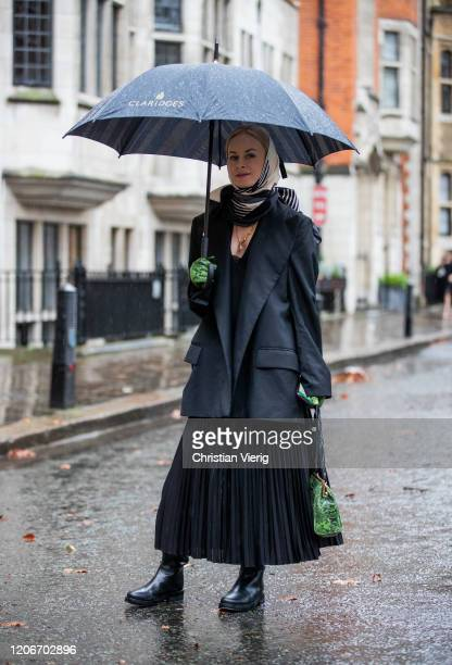 Thora Valdimars is seen wearing headscarf, black blazer, pleated dress, green bag and gloves with snake print outside Preen during London Fashion...