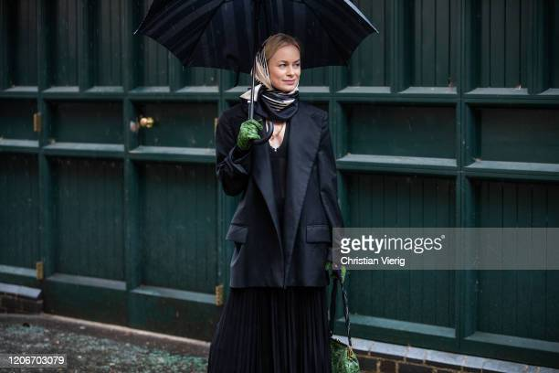 Thora Valdimars is seen wearing headscarf black blazer pleated dress green bag and gloves with snake print outside Preen during London Fashion Week...
