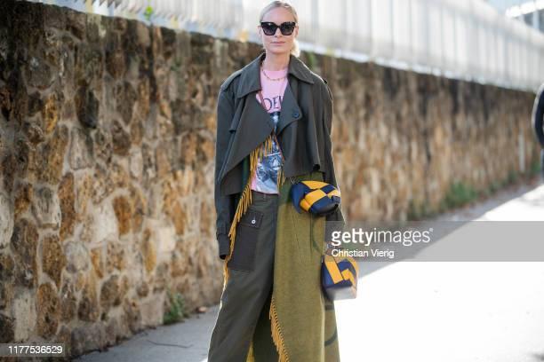 Thora Valdimars seen wearing khaki pants, cape, coat, striped Loewe bag, pink shirt with print outside Loewe during Paris Fashion Week Womenswear...