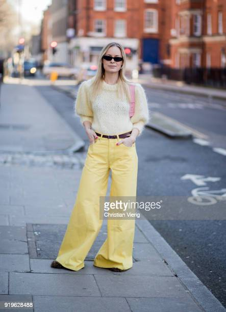 Thora Valdimars wearing yellow flared pants knit seen outside JW Anderson during London Fashion Week February 2018 on February 17 2018 in London...