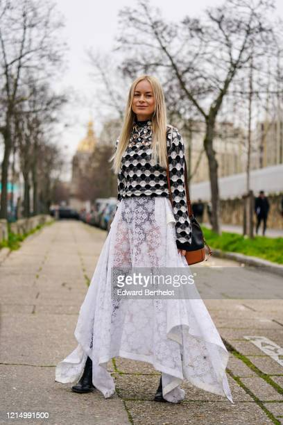 Thora Valdimars wears a black and white bejeweled top with geometric patterns, a white lace mesh skirt, a black and brown leather Loewe bag, black...
