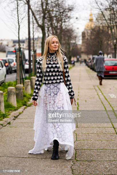 Thora Valdimars wears a black and white bejeweled top with geometric patterns, a white lace mesh skirt, black leather boots, outside Loewe, during...