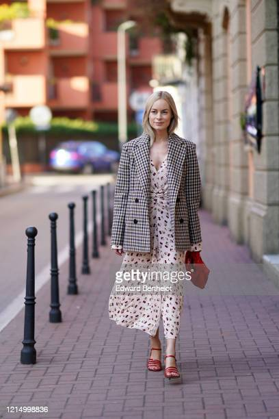 Thora Valdimars wears a black and white checked pattern oversized blazer jacket a white floral print low neck dress a red woven leather Bottega...