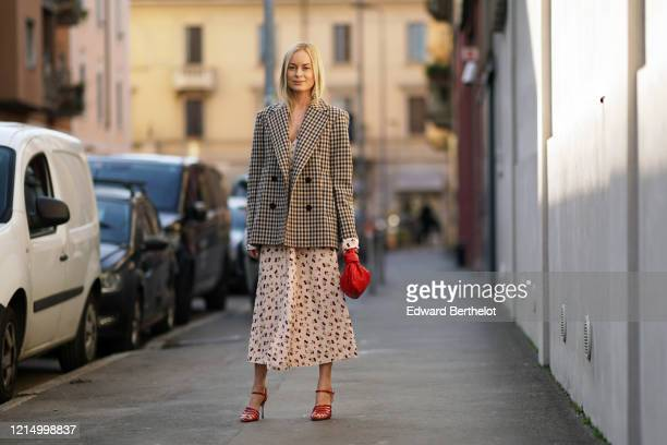 Thora Valdimars wears a black and white checked pattern oversized blazer jacket, a white floral print low neck dress, a red woven leather Bottega...