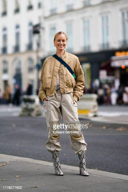 Thora Valdimars wears a cream color bomber jacket, a shoulder strapped bag, gray pants with cargo pockets, snake print pattern boots, outside...