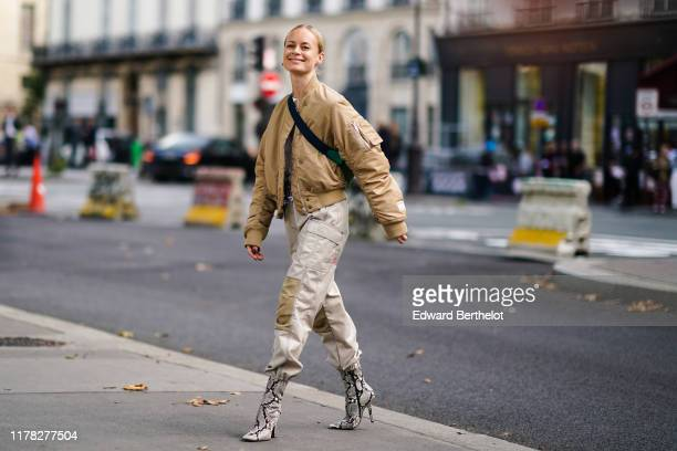 Thora Valdimars wears a cream color bomber jacket a shoulder strapped bag gray pants with cargo pockets snake print pattern boots outside Beautiful...