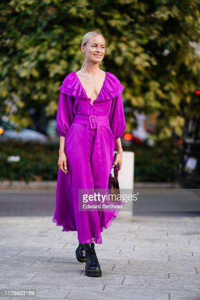 Thora Valdimars wears a low neck ruffled purple dress with a belt a brown leather bag black leather shoes outside the Alberta Ferretti show during...