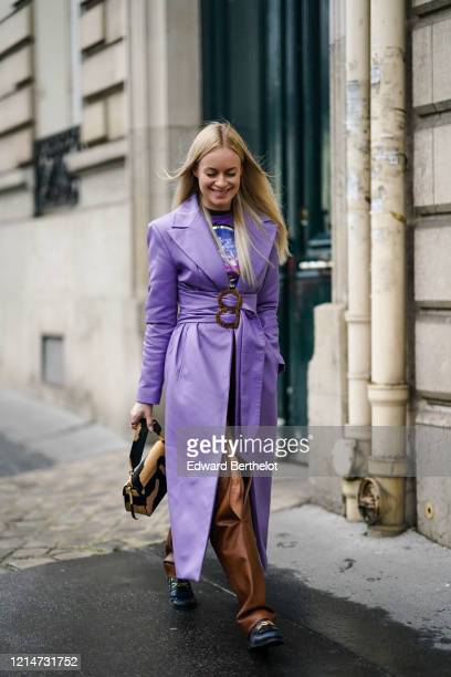 Thora Valdimars wears a purple leather trench coat with a belt a colored tshirt brown leather pants a beige and black bag black leather shoes outside...