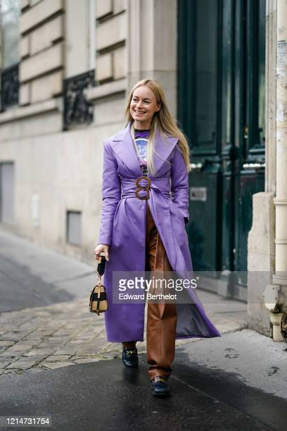 Thora Valdimars wears a purple leather trench coat with a belt, a colored t-shirt, brown leather pants, a beige and black bag, black leather shoes,...