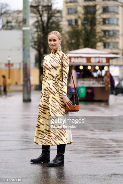 Thora Valdimars wears silver metallic earrings, a yellow and brown zebra pattern printed dress, a black and brown leather bag from Loewe, black...