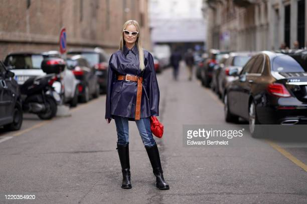 Thora Valdimars wears white sunglasses, a dark navy blue/purple leather coat, a brown belt, a red woven leather Bottega Veneta bag, blue denim jeans,...