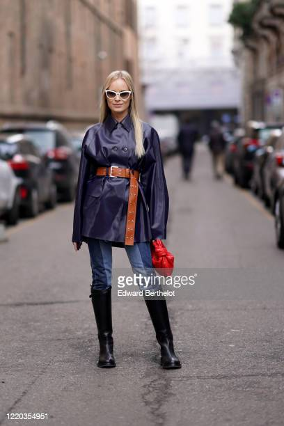 Thora Valdimars wears white sunglasses, a dark navy blue/purple leather coat, a brown belt, a red woven leather Bottega Veneta bag, blue denim jeans,...