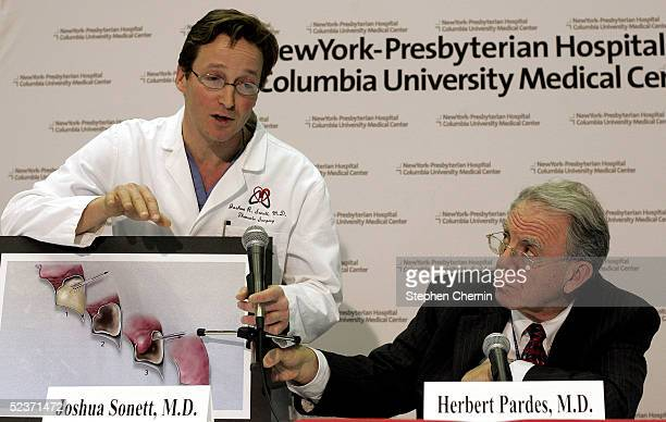 Thoracic surgeon Dr Joshua Sonett assisted by New York Presbyterian Hospital president and CEO Dr Herbert Pardes holds a crosssection diagram of a...
