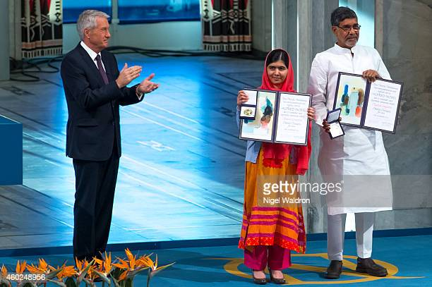 Thorbjorn Jagland of Norway applauds Malala Yousafzai and Kailash Satyarthi as they accept their Nobel Peace Prize Awards during the Nobel Peace...