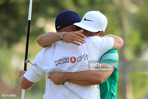 Thorbjorn Olesen of Denmark celebrates victory on the 18th green with caddie Dominic Bott during day four of the Turkish Airlines Open at the Regnum...