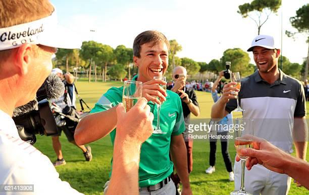 Thorbjorn Olesen of Denmark celebrates with champagne and his fellow Danish golfers Lucas Bjerregaard and Soren Kjeldsen following his victory during...