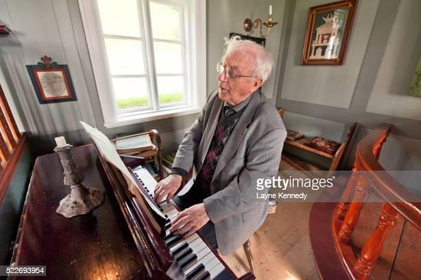Thordur Tomasson plays the organ at Skogar Folk Museum, Iceland