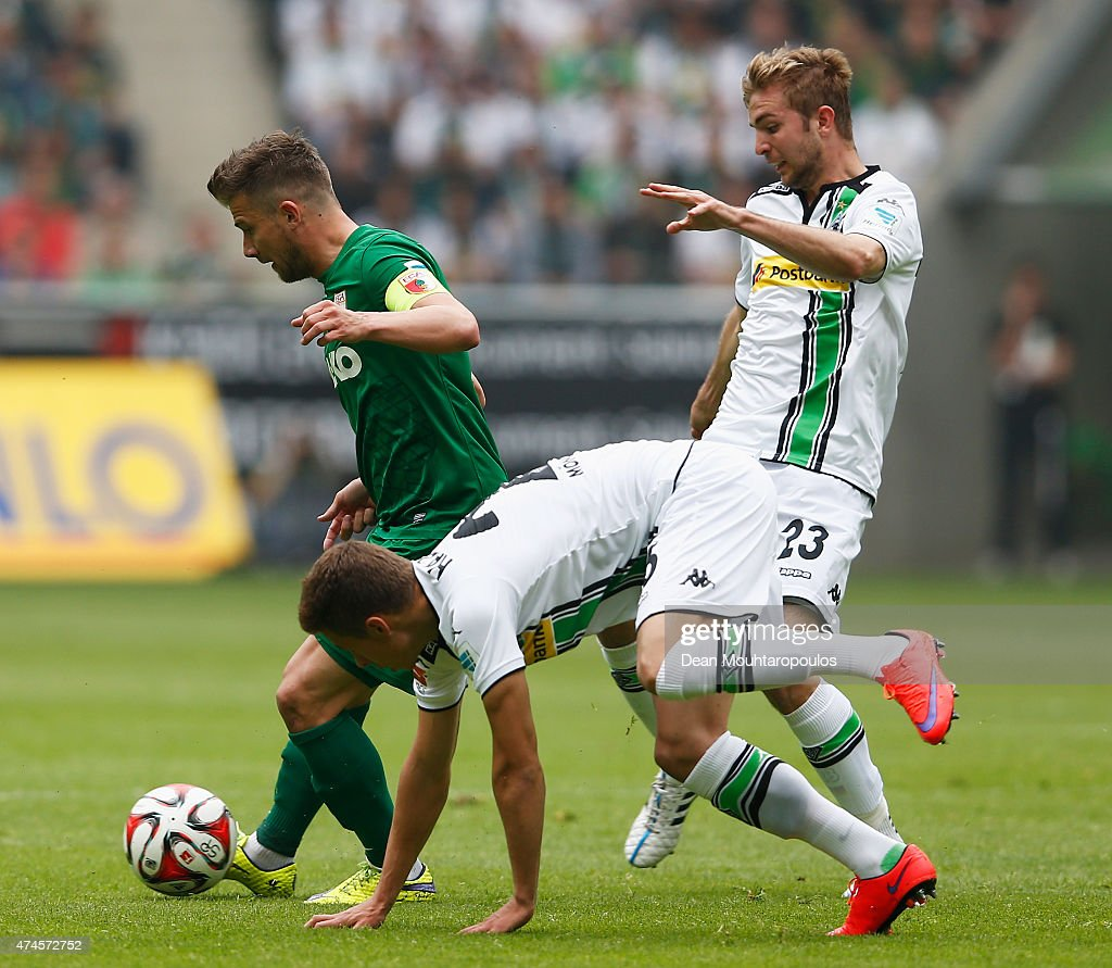 Thorgan Hazard (C) and Christoph Kramer (R) of Borussia Moenchengladbach chase Daniel Baier of FC Augsburg during the Bundesliga match between Borussia Moenchengladbach and FC Augsburg held at Borussia Park Stadium on May 23, 2015 in Moenchengladbach, Germany.