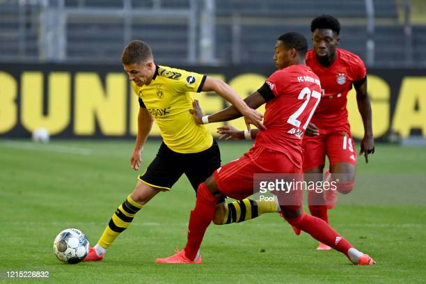 Thorgan Hazard of Borussia Dortmund is challenged by David Alaba and Alphonso Davies of Bayern Munich during the Bundesliga match between Borussia...