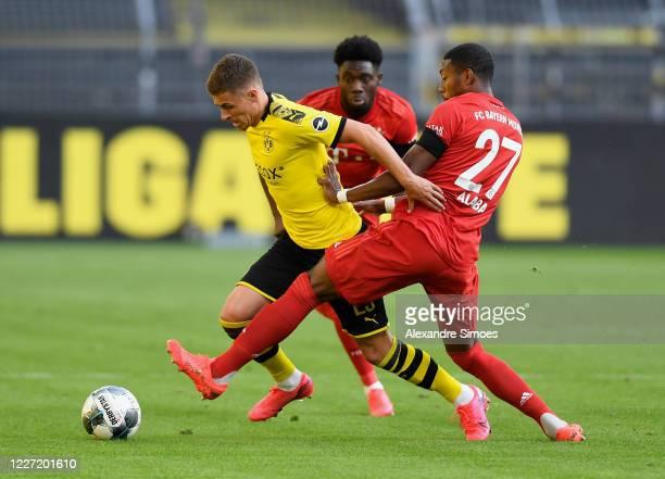 Thorgan Hazard of Borussia Dortmund is challenged by David Alaba of Bayern Muenchen whilst Alphonso Davies of Bayern Muenchen looks on during the...