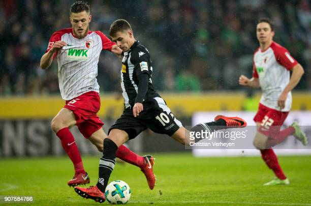 Thorgan Hazard of Borussia Moenchengladbach and Jeffrey Gouweleeuw of FC Augsburg battle for the ball during the Bundesliga match between Borussia...