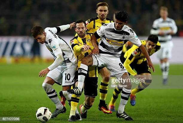 Thorgan Hazard of Borussia Moenchengladbach and Mahmoud Dahoud of Borussia Moenchengladbach challenge Gonzalo Castro of Borussia Dortmund during the...