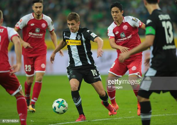 Thorgan Hazard of Borussia Moenchengladbach and Suat Serdar of FSV Mainz 05 and Yoshinori Muto of FSV Mainz 05 battle for the ball during the...