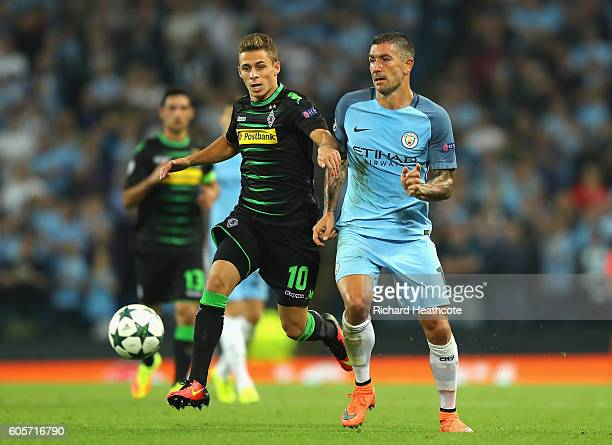 Thorgan Hazard of Borussia Moenchengladbach holds off Aleksander Kolorov of Manchester City during the UEFA Champions League match between Manchester...
