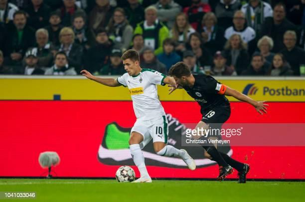 Thorgan Hazard of Borussia Moenchengladbach is chased by David Abraham of Eintracht Frankfurt during the Bundesliga match between Borussia...