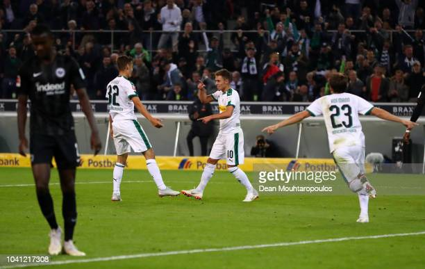 Thorgan Hazard of Borussia Monchengladbach celebtrates with team mate Florian Neuhaus after scoring his team's second goal during the Bundesliga...