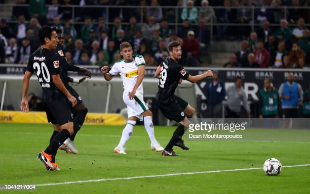 Thorgan Hazard of Borussia Monchengladbach scores his team's second goal past David Abraham of Eintracht Frankfurt during the Bundesliga match...
