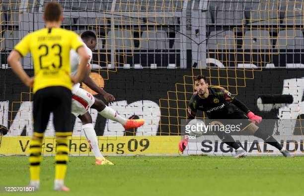 Thorgan Hazard of Dortmund watches while Jean-Philippe Mateta of Mainz scores his sides second goal from the penalty spot against goalkeeper Roman...