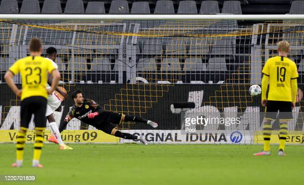 Thorgan Hazard of Dortmund watches while Jean-Philippe Mateta of Mainz scores the 0-2 by penalty against goalkeeper Roman Buerki of Dortmund during...