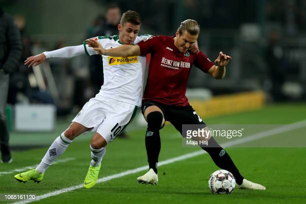 Thorgan Hazard of Gladbach challenges Matthias Ostrzolek of Hannover during the Bundesliga match between Borussia Moenchengladbach and Hannover 96 at...