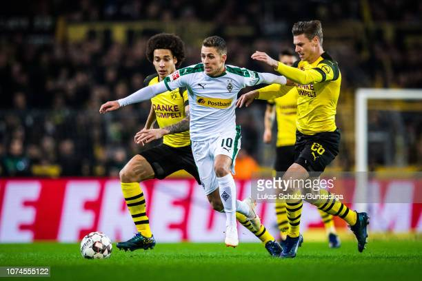 Thorgan Hazard of Moenchengladbach challenges for the ball with Axel Witsel an Lukasz Piszczek of Dortmund during the Bundesliga match between...