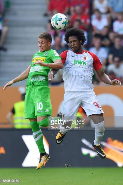 Thorgan Hazard of Moenchengladbach fights for the ball with Caiuby of Augsburg during the Bundesliga match between FC Augsburg and Borussia...
