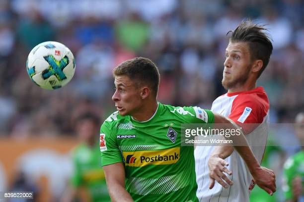 Thorgan Hazard of Moenchengladbach fights for the ball with Jeffrey Gouweleeuw of Augsburg during the Bundesliga match between FC Augsburg and...