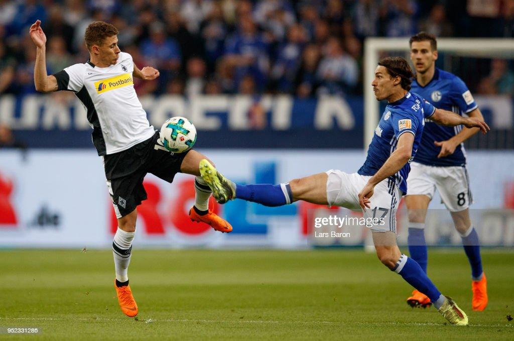 Thorgan Hazard of Moenchengladbach is challenged by Benjamin Stambouli of Schalke during the Bundesliga match between FC Schalke 04 and Borussia Moenchengladbach at Veltins-Arena on April 28, 2018 in Gelsenkirchen, Germany.