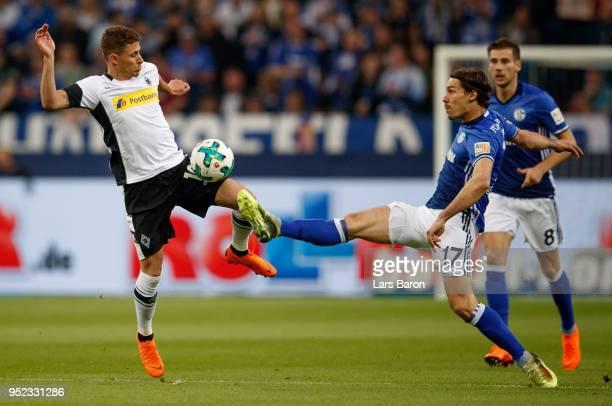 Thorgan Hazard of Moenchengladbach is challenged by Benjamin Stambouli of Schalke during the Bundesliga match between FC Schalke 04 and Borussia...