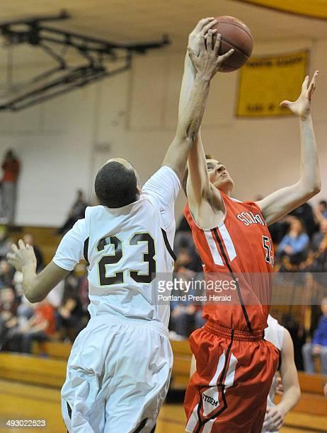 Thornton Academy vs Scarborough boys basketball game TA's Corey Hart and Scarborough's Jacob Gardner vie for a rebound Tuesday February 4 2014