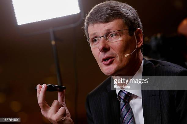 Thorsten Heins chief excutive officer of BlackBerry holds a Q10 smartphone while speaking during a Bloomberg Television interview at the annual...