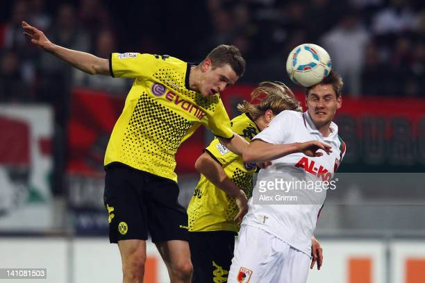 Thorsten Oehrl of Augsburg jumps for a header with Marcel Schmelzer and Sven Bender of Dortmund during the Bundesliga match between FC Augsburg and...
